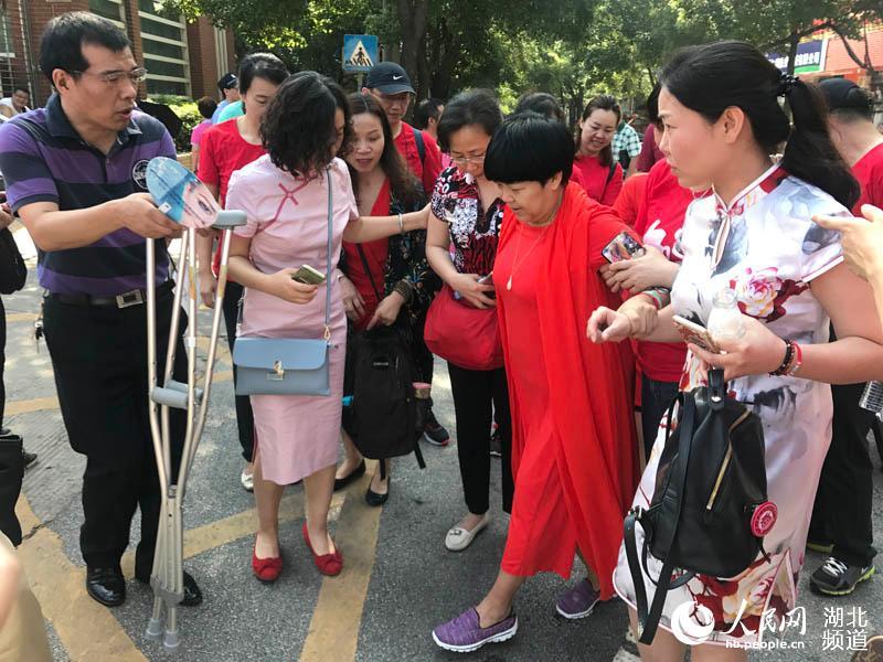 助力高考:家长穿旗袍陪考 教养员背靠轮椅递送考