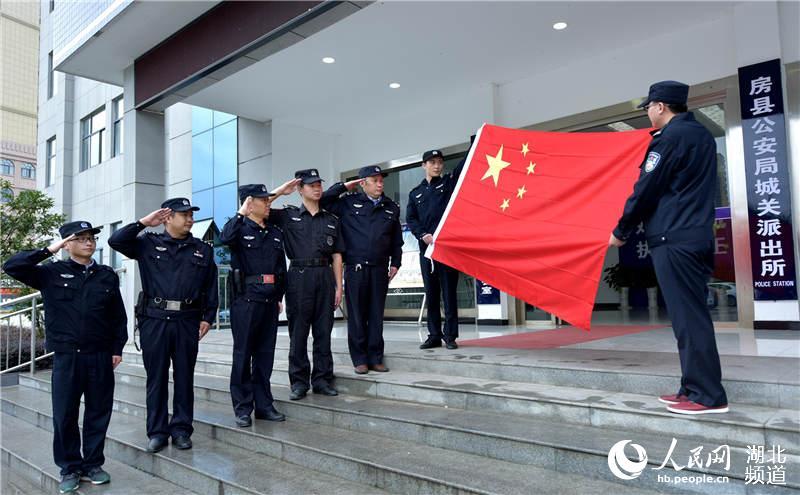 基层派出所民警向国旗敬礼,庆祝新中国成立68周年,决心以最饱