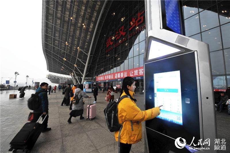 """旅客正在使用""""智慧岛""""终端一体机查询乘车信息。(钟明 摄)"""