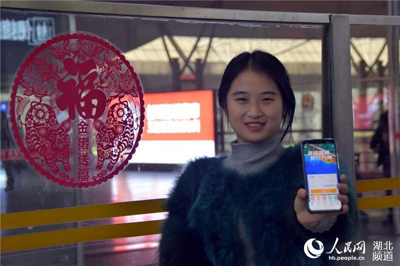 """旅客手持""""畅行九州""""APP享受""""智慧车站""""服务。(陈俊 摄)"""