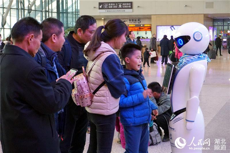 """旅客正在通过与""""头雁宝宝""""机器人对话查询服务信息。(钟明 摄)"""