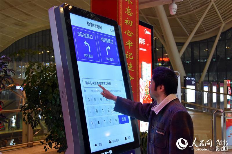 """旅客正在使用""""畅行九州""""APP智能查询机查询检票口信息。(钟明 摄)"""