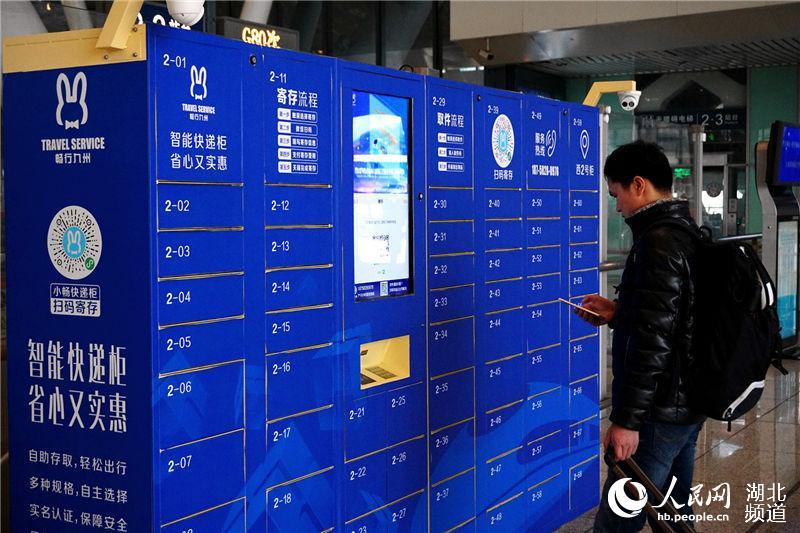 旅客在武汉火车站通过手机扫码使用智能储物柜寄存行李物品。(钟明 摄)