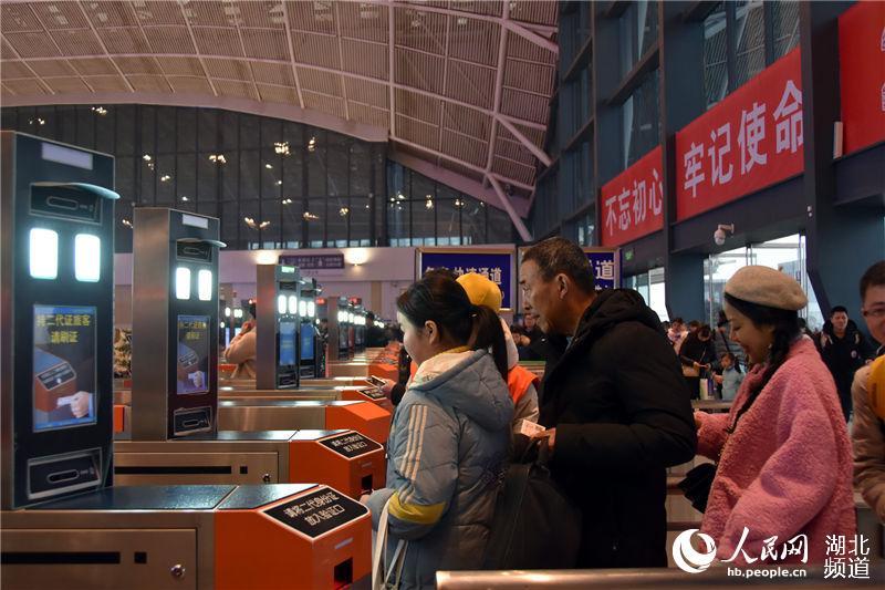 """旅客正在通过""""刷脸""""实名制验证闸机进站。(钟明 摄)"""