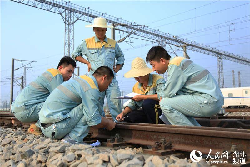 图为武汉高铁工务段职工在高铁动车基地检查道岔 (孟家豪 摄)