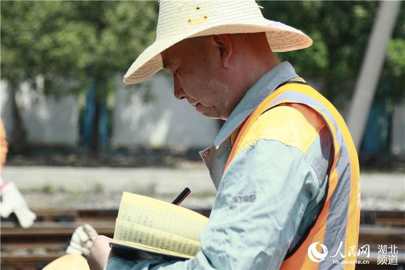 图为武汉高铁工务段职工在动车基地记录检查数据 (孟家豪 摄)