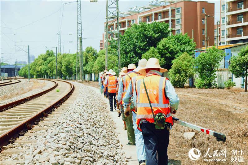 图为武汉高铁工务段职工在高铁动车基地进行高温巡查作业 (孟家豪 摄)