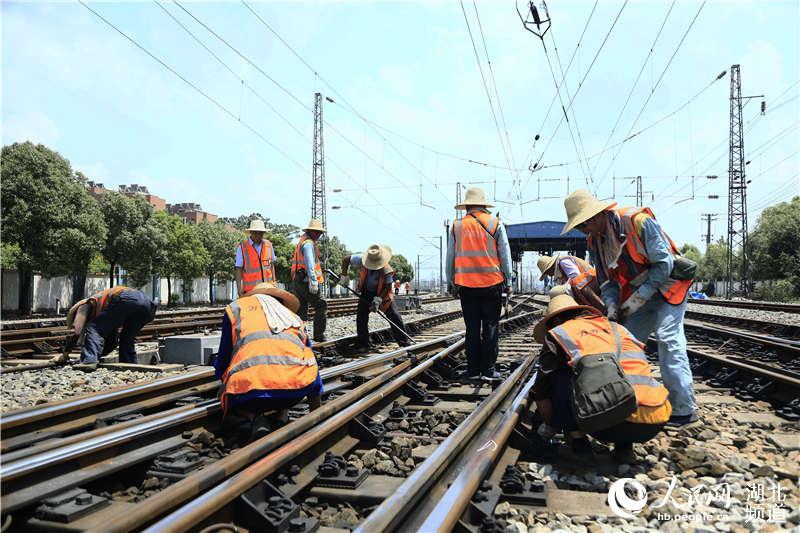 图为武汉高铁工务段职工在高铁动车基地进行大修施工作业 (孟家豪 摄)