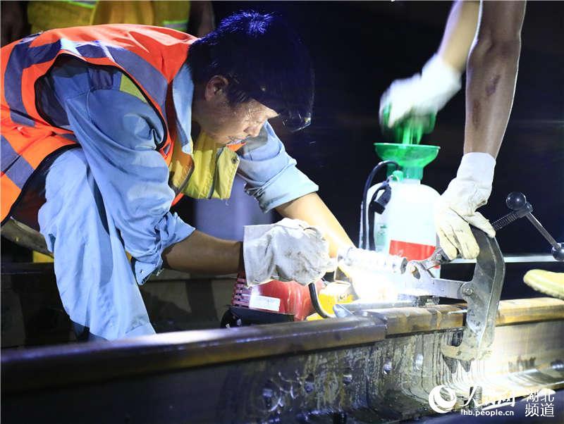 图为武汉高铁工务段职工在货车外绕线上对钢轨进行钻孔作业 (孟家豪 摄)
