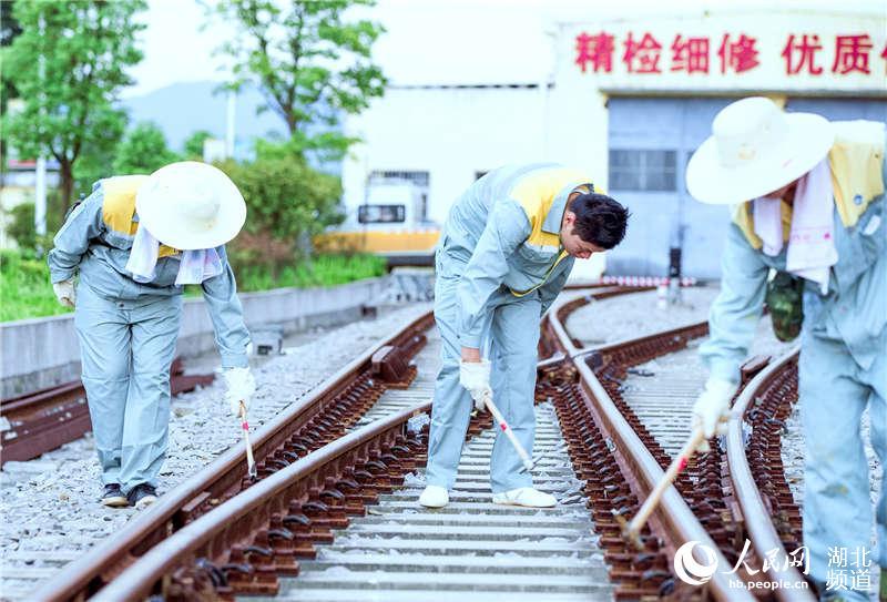 图为武汉高铁工务段职工在五九客专站区进行道岔螺栓检查 (孟家豪 摄)