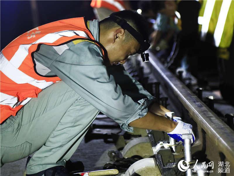 图为武汉高铁工务段职工在武冈城际线上安装钢轨紧固件 (孟家豪 摄)