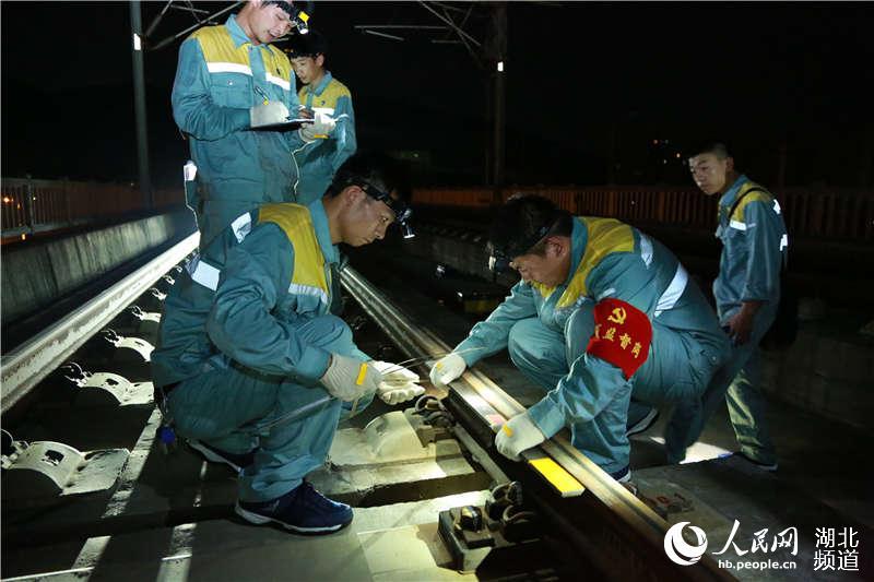 图为武汉高铁工务段职工在京广高铁线上对钢轨焊缝进行检查 (孟家豪 摄)