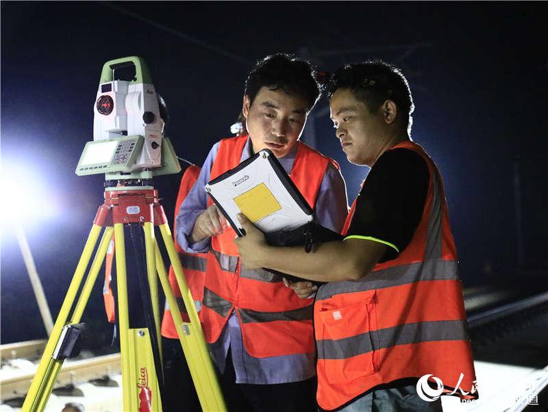 图为武汉高铁工务段职工在武冈城际线上测量线路轨距 (孟家豪 摄)
