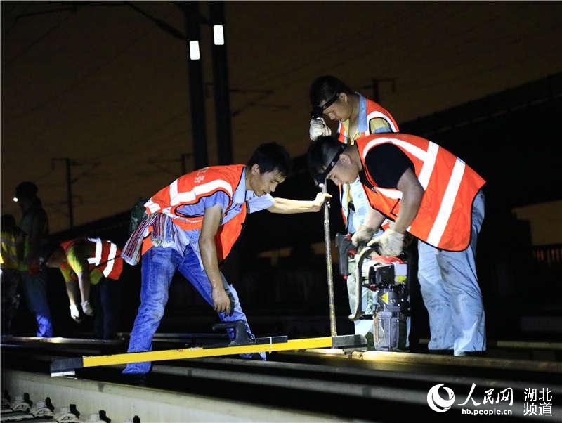 图为武汉高铁工务段职工在货车外绕线上进行线路整治作业 (孟家豪 摄)