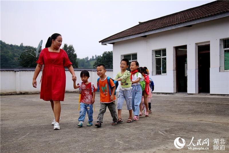 2019年9月1日,在湖北省十堰市郧阳区五峰乡东峰村教学点,放学后,教师王婧带领学生走出教室。